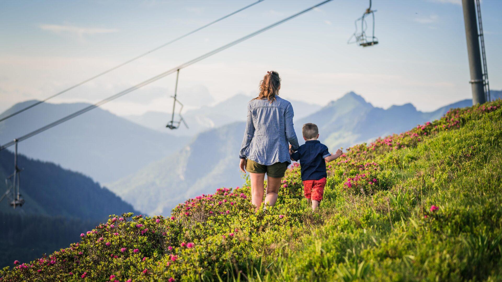 Femme et son fils se promenant en été en montagne avec télésièges derrière