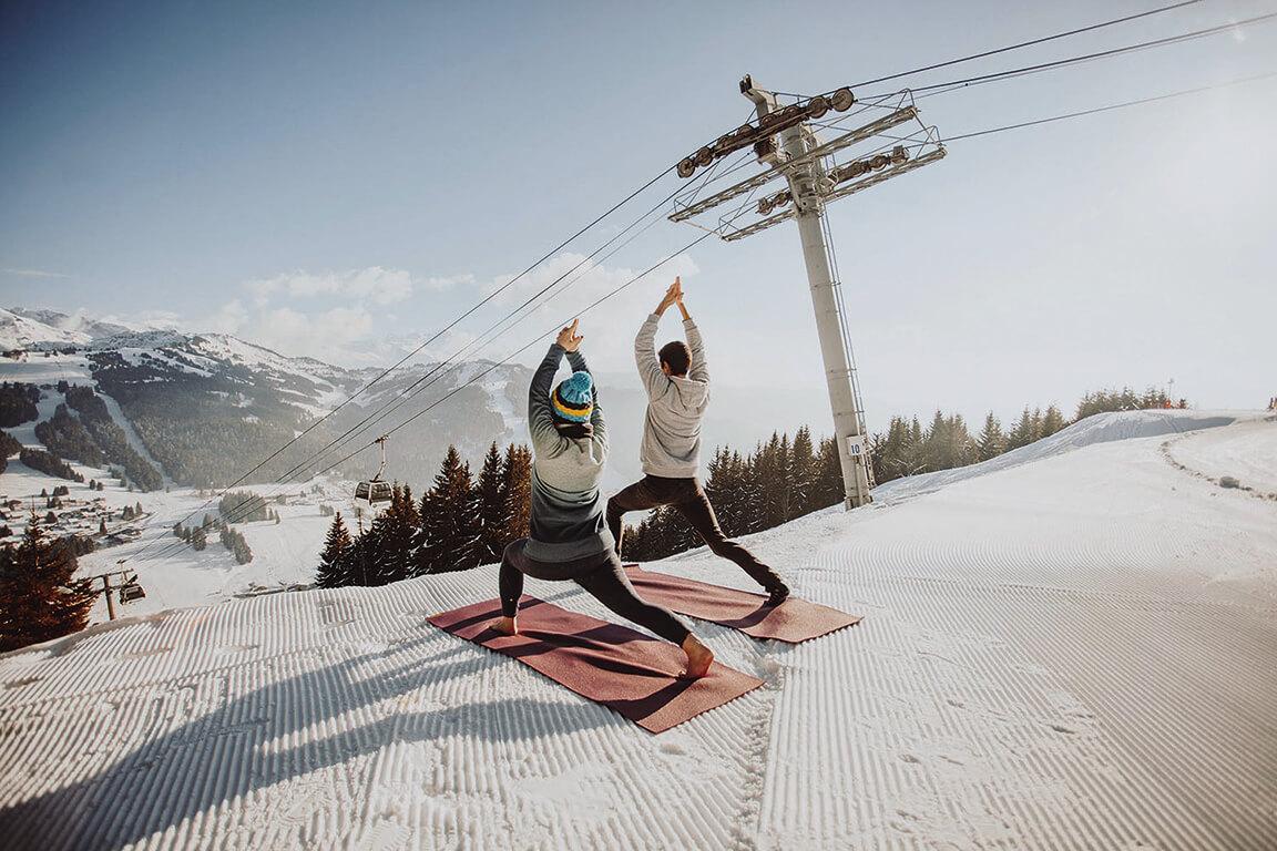 Deux personnes faisant du yoga en hiver avec télécabine derrière