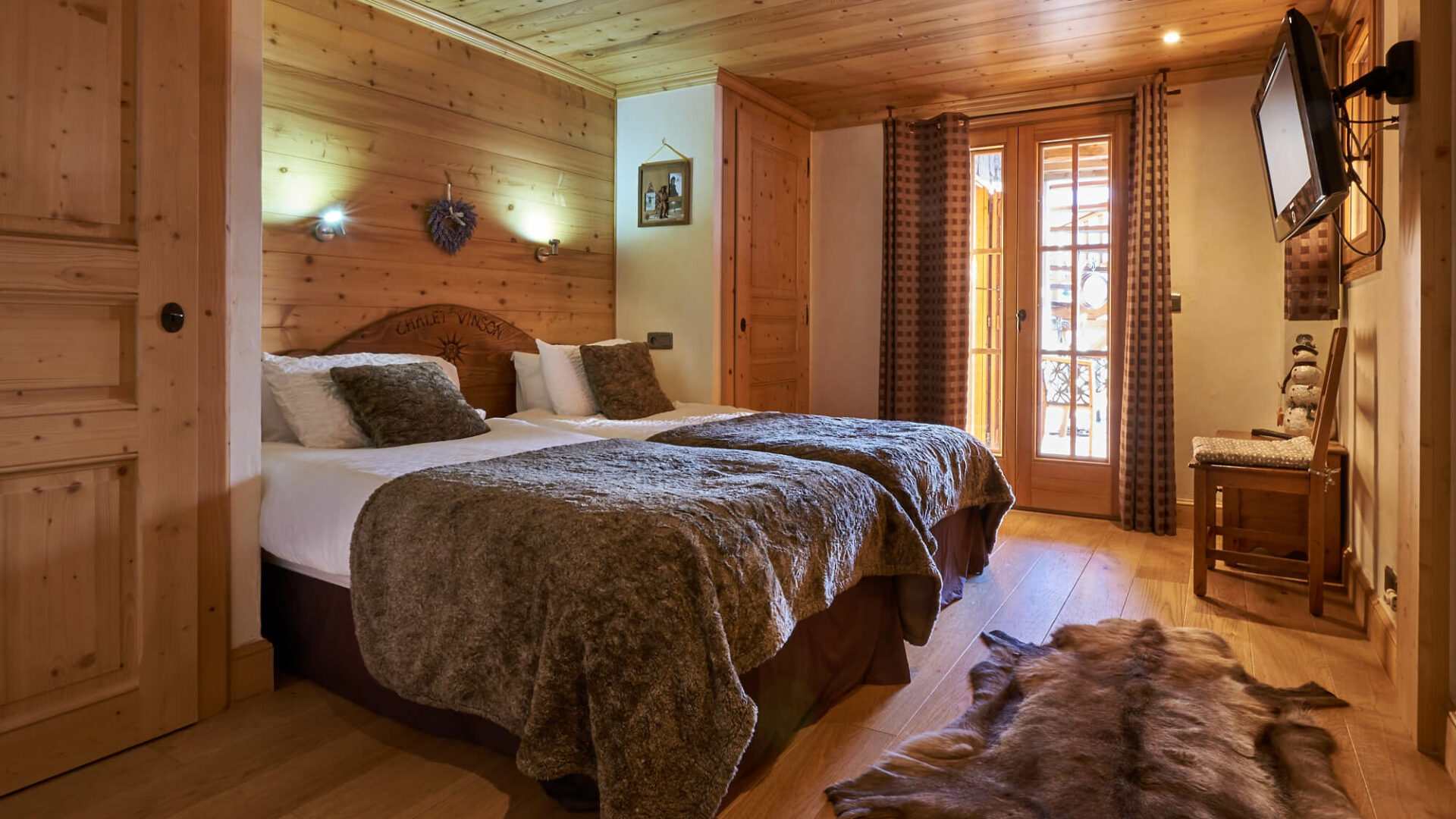 Chambre d'hôtel avec deux lits simples, tout en bois et peau de bête