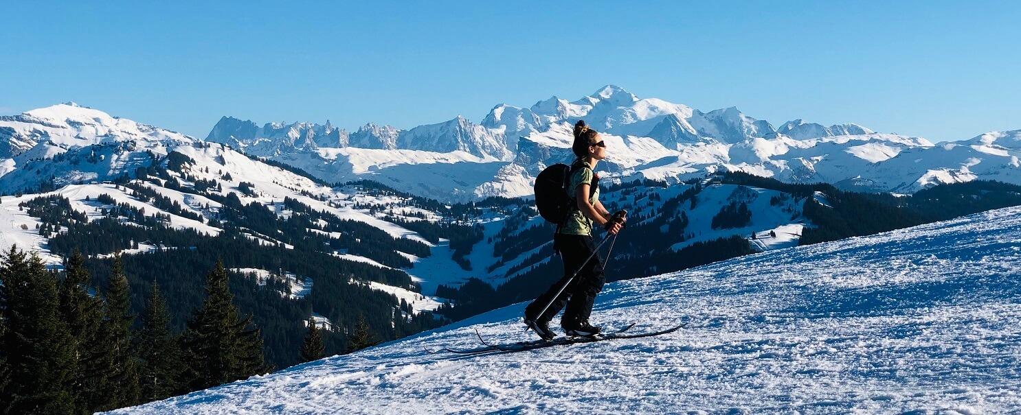 Femme faisant du ski de randonnée en hiver avec paysage montagnes derrière