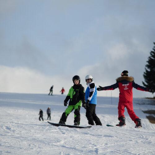 Vacanciers prenant un cours de snowboard avec un moniteur