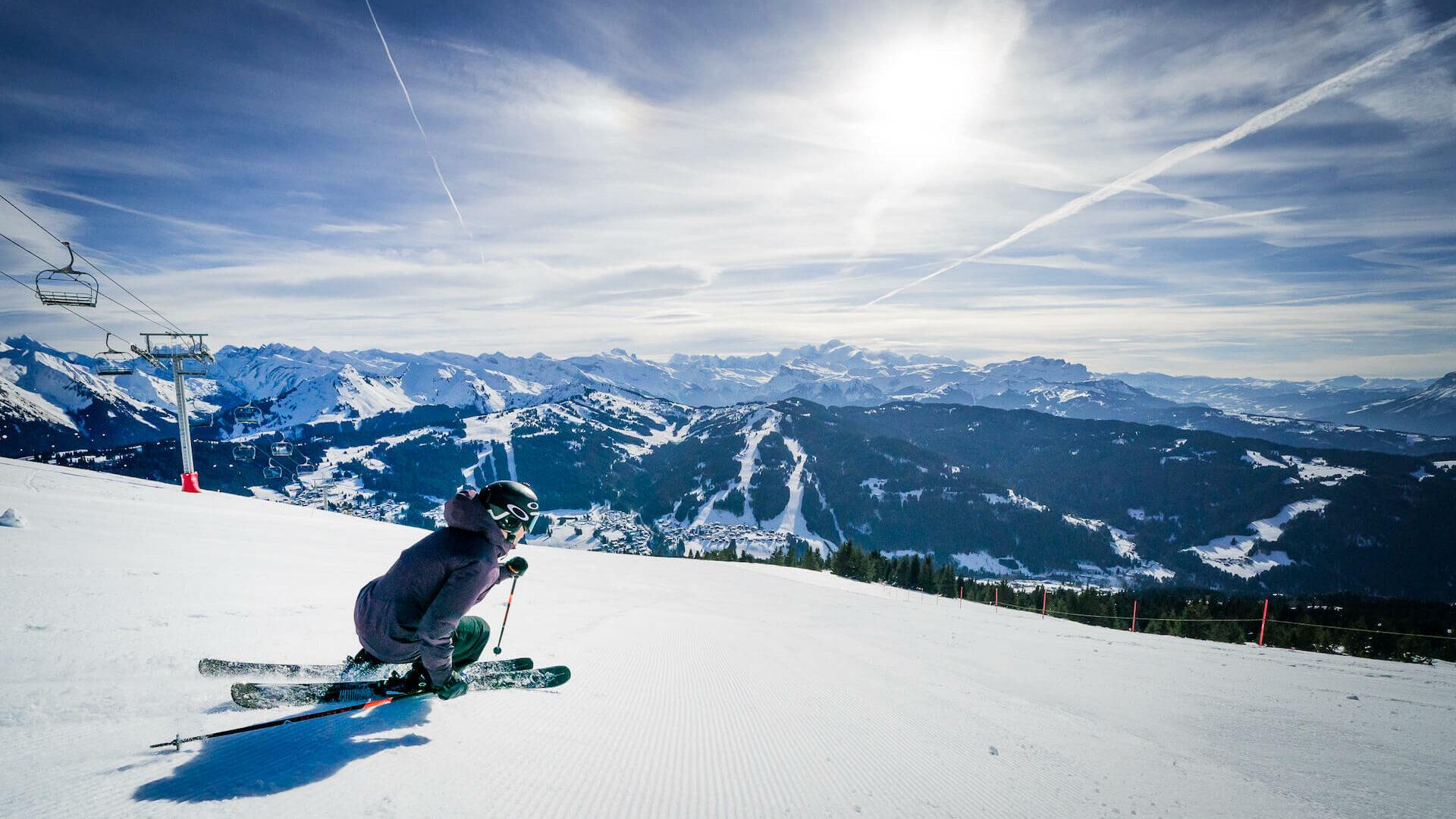 Skieur descendant une piste avec montagne et télésiège en fond