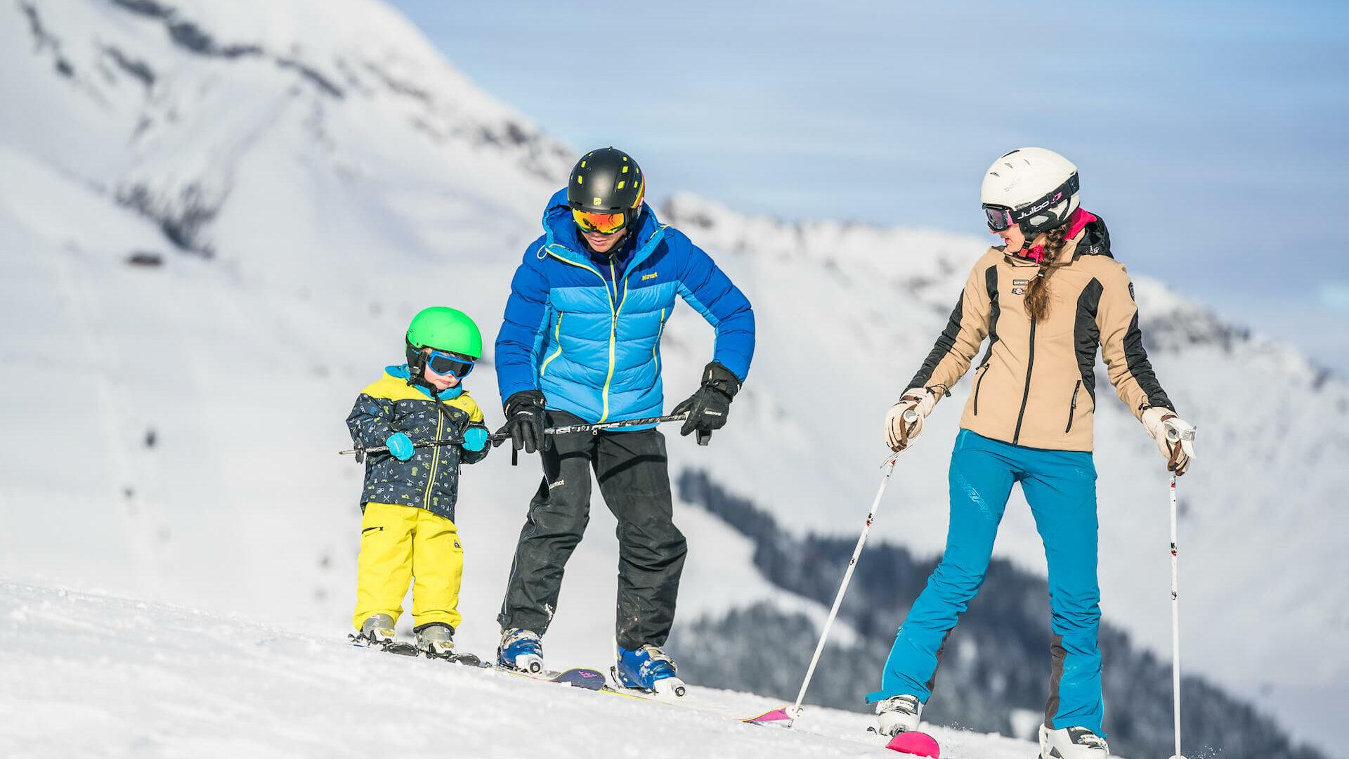 Famille en ski avec parents qui apprennent à leur enfant à skier
