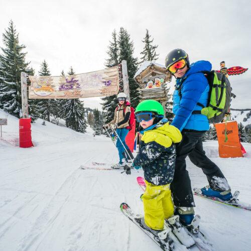 Famille en ski en hiver au départ d'une piste sur le thème des indiens