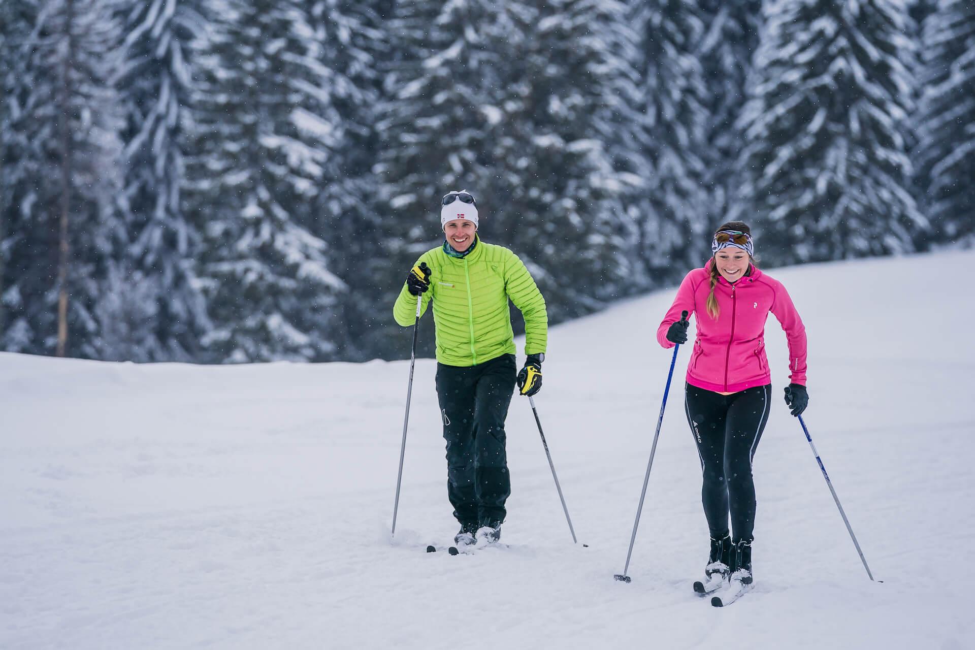Couple faisant du ski de fond avec neige qui tombe