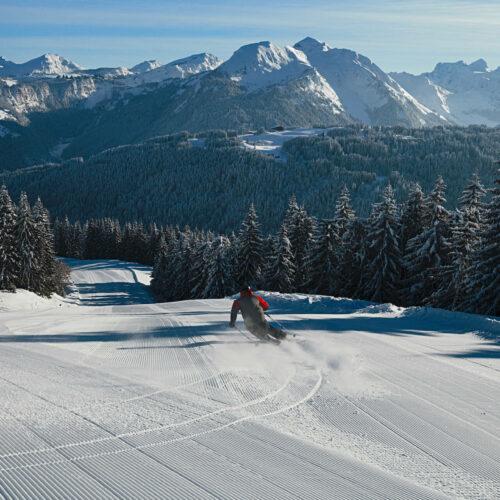 Skieur descendant une piste avec forêt derrière
