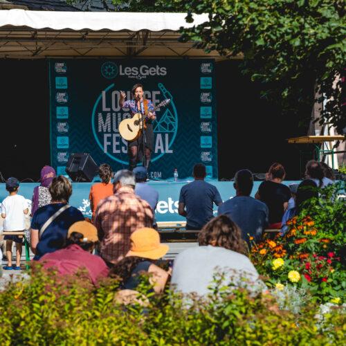 Chanteuse sur une scène avec une guitare avec des spectateurs et des fleurs en premier plan