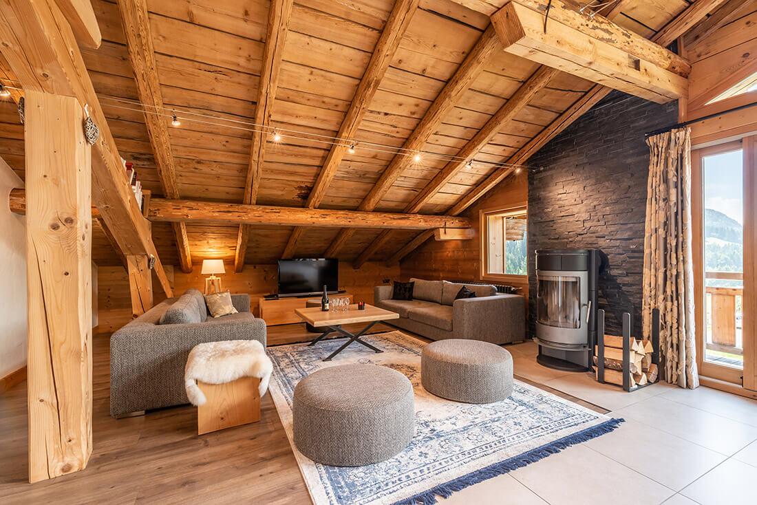 Salon chalet avec cheminée, canapés, tabourets, télévision et poutres apparentes