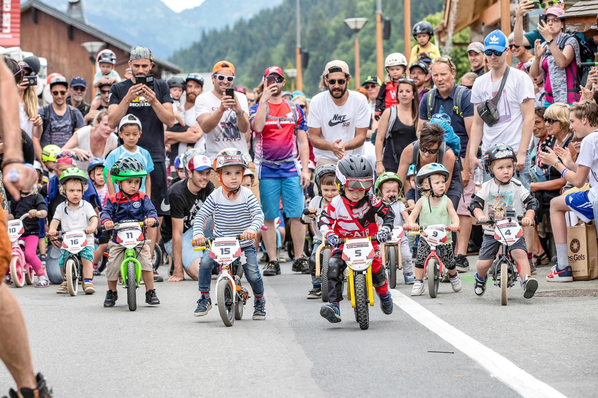 Petits enfants faisant une course de vélo avec parents les encourageant derrière