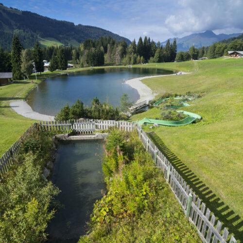 Vue d'ensemble d'un lac de montagne en été avec pelouses, toboggan et réserve d'eau