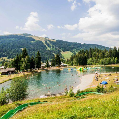 Lac de montagne en été avec jeu gonflable et toboggan