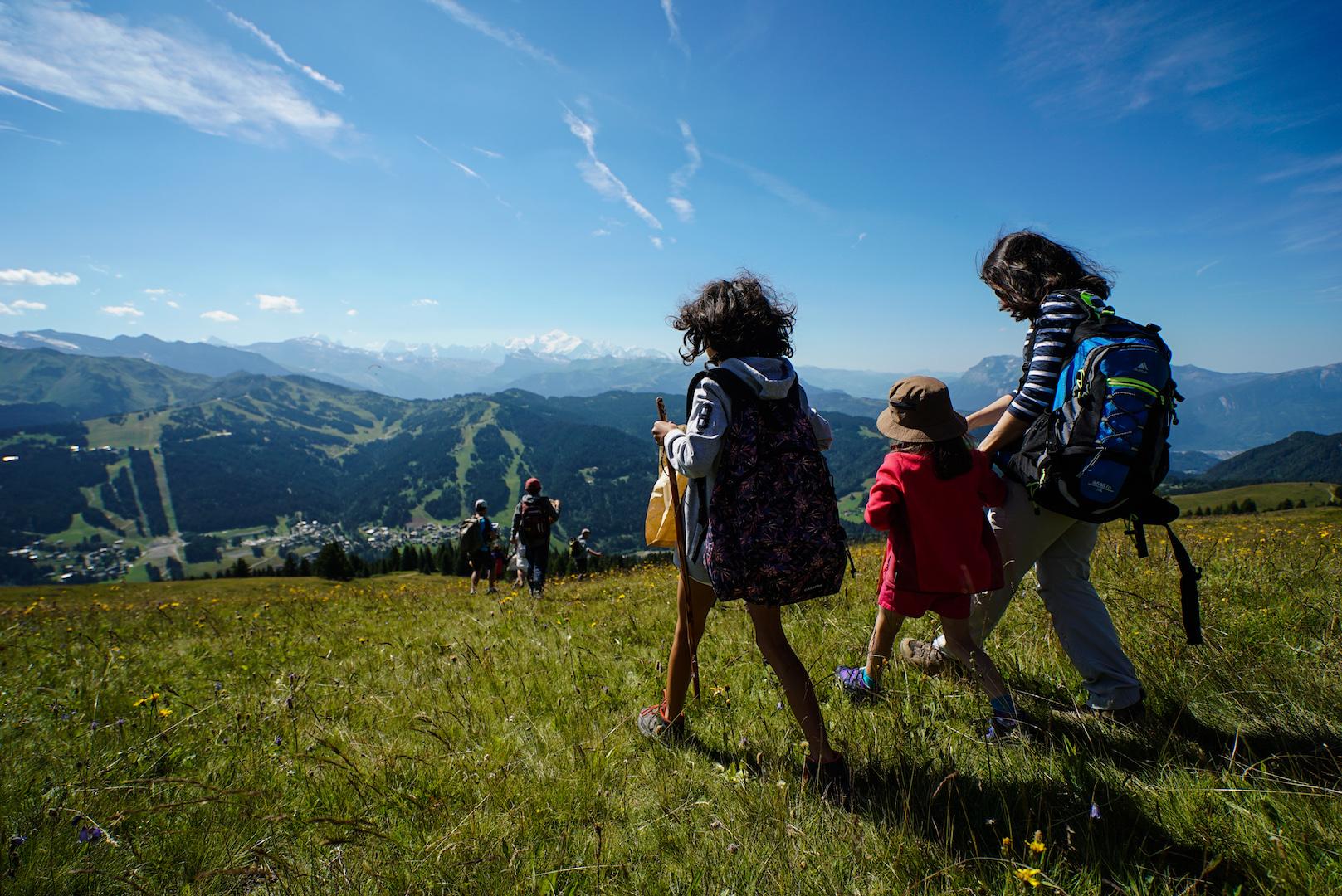 Famille faisant une balade en été avec montagnes, ciel bleu et prairie en fond