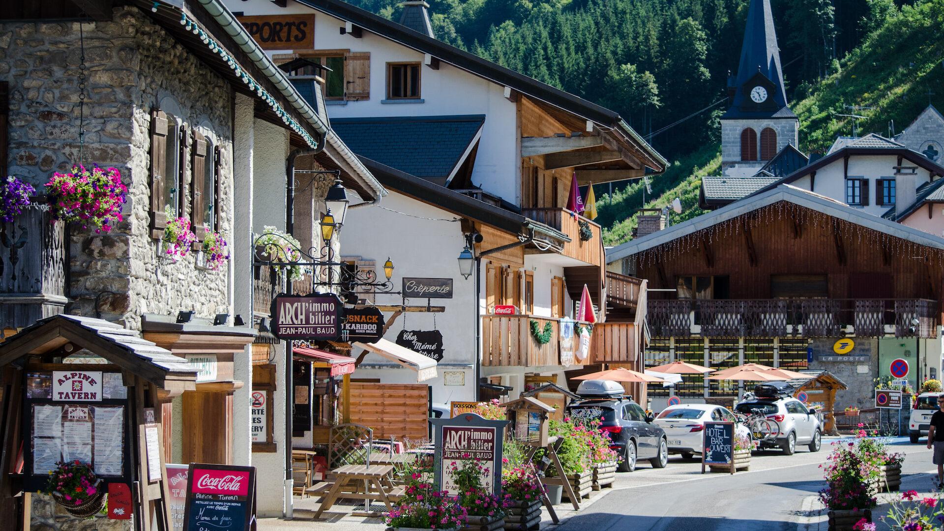 Rue vieux village des Gets en été avec église au fond