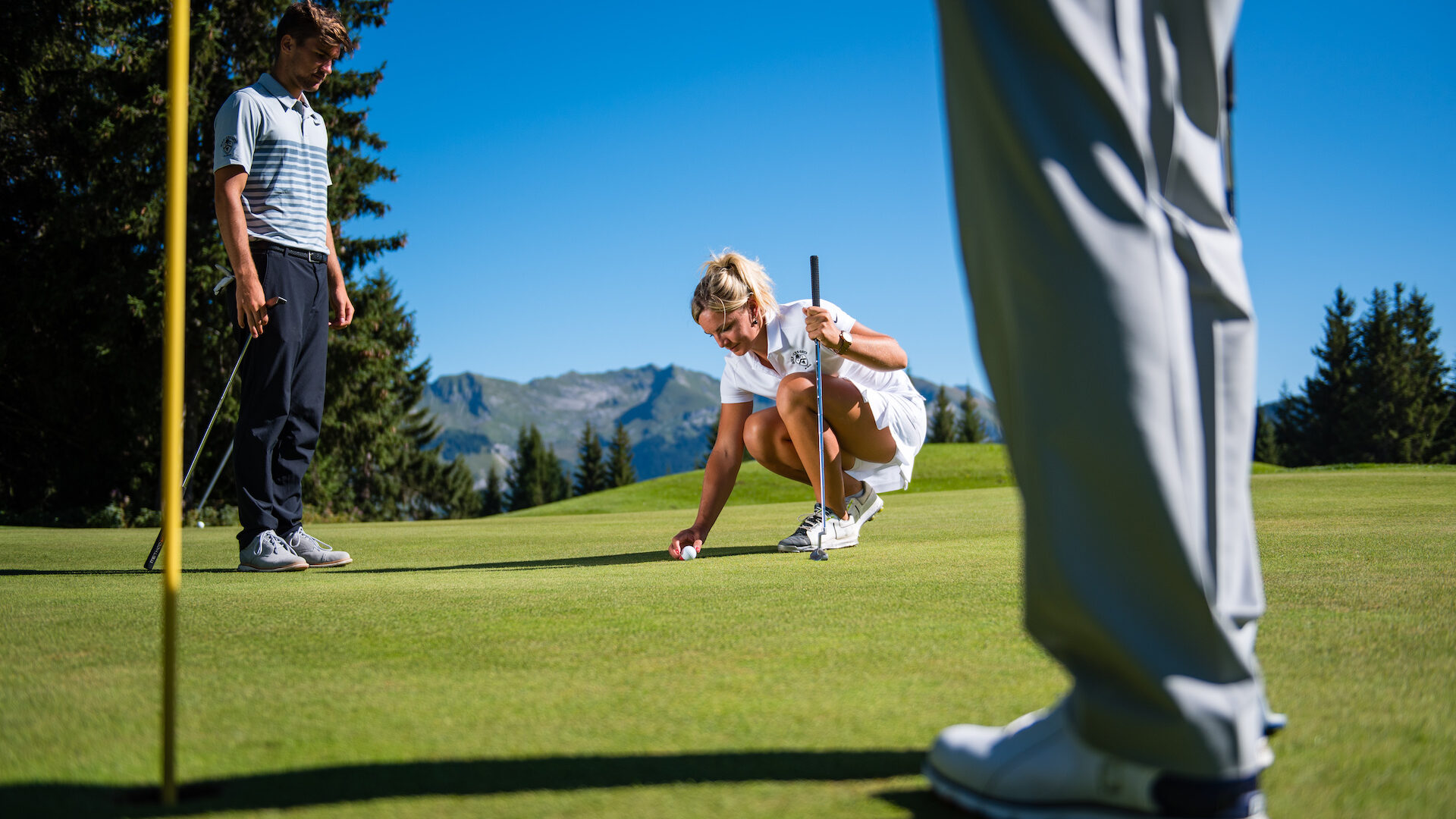 Three people playing golf with a woman putting the ball down.