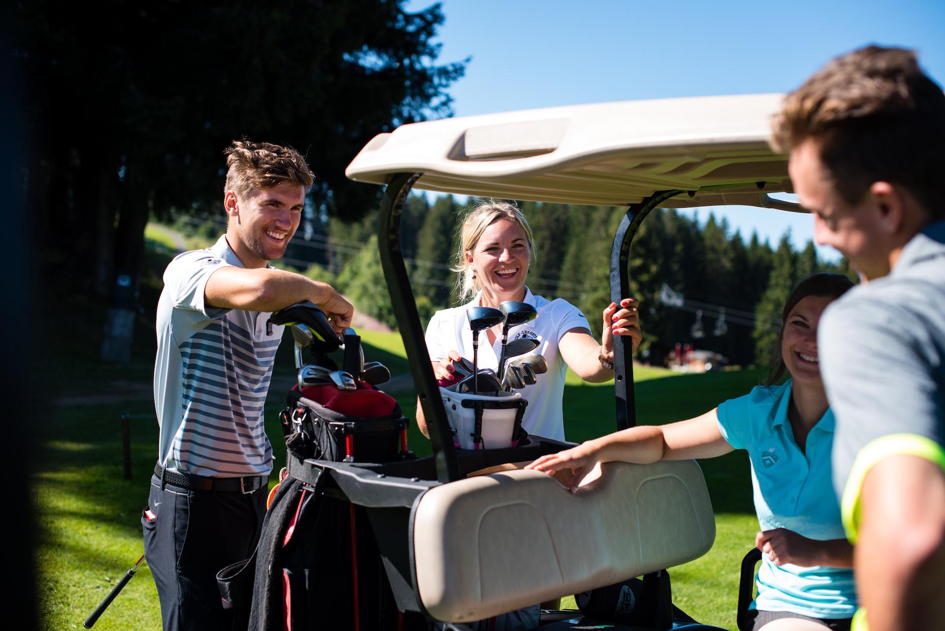 Groupe d'amis parlant et souriant à côté d'une voiturette de golf avec leur matériel