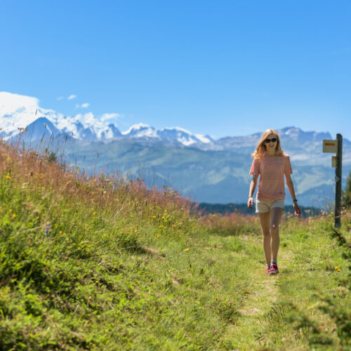 Woman walking on a path in summer with Mont-Blanc in the background