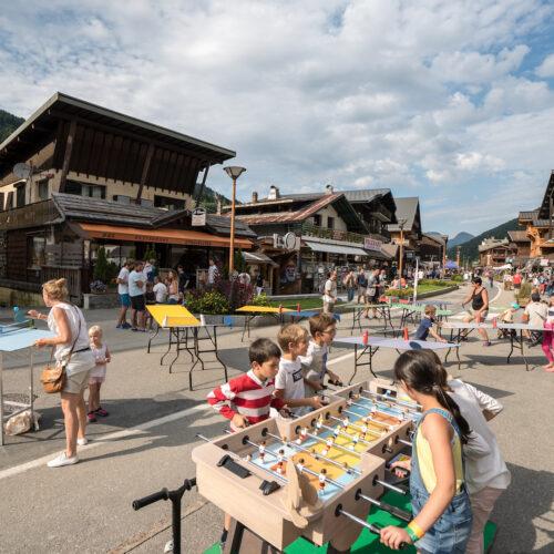 Vacanciers jouant à divers jeux : babyfoot, ping-pong...dans la rue du Centre des Gets
