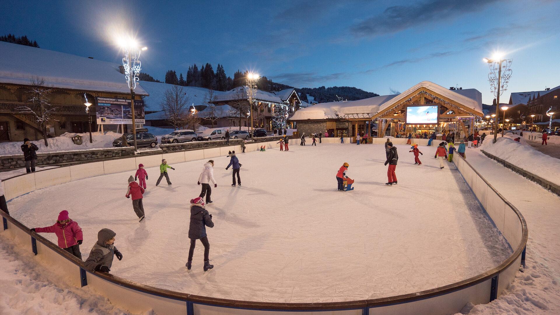 Personnes sur la patinoire en soirée en hiver