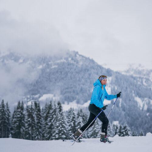 Femme faisant une balade en raquettes en hiver avec la montagne en fond
