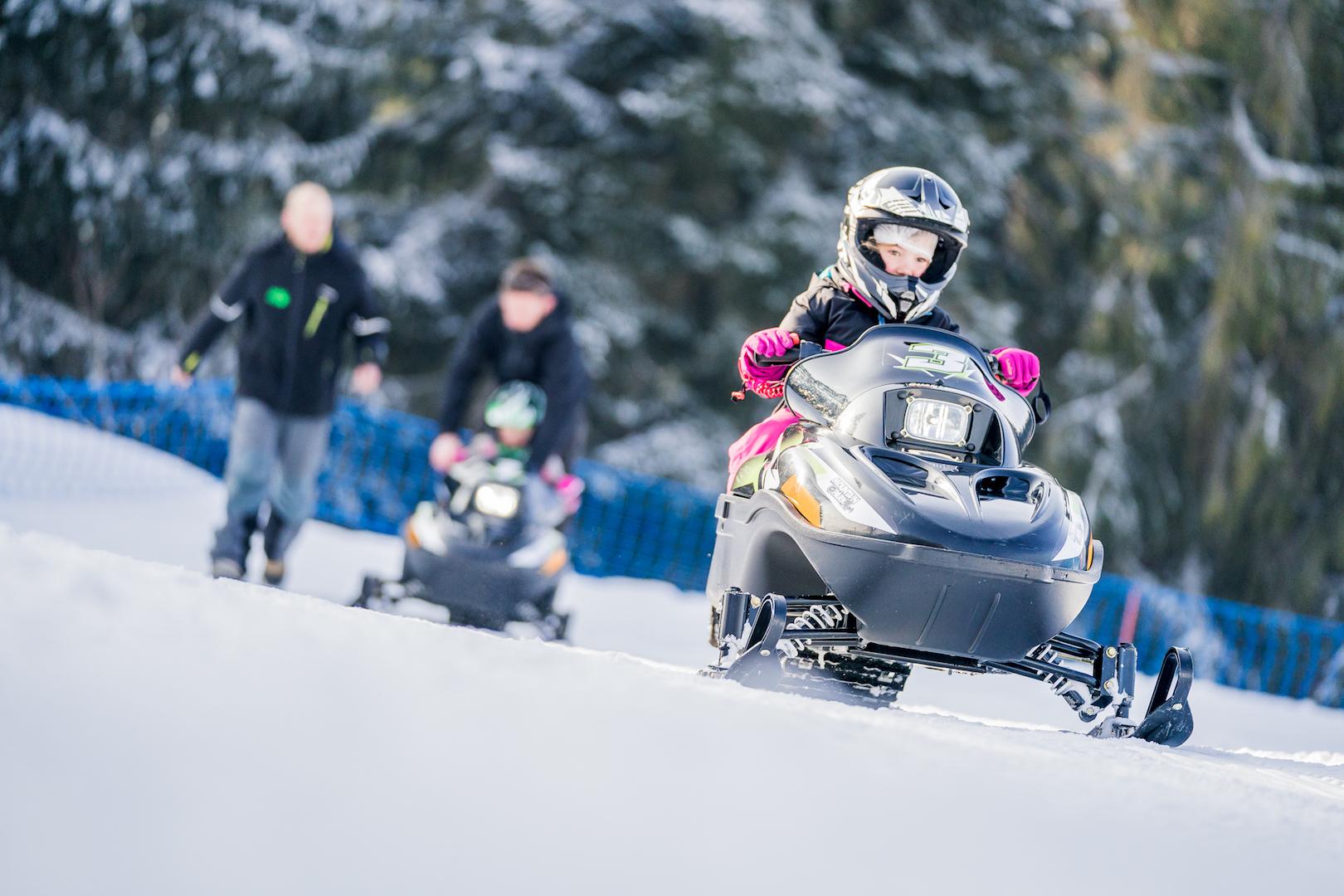 Enfants faisant de la motoneige en compagnie de leurs parents