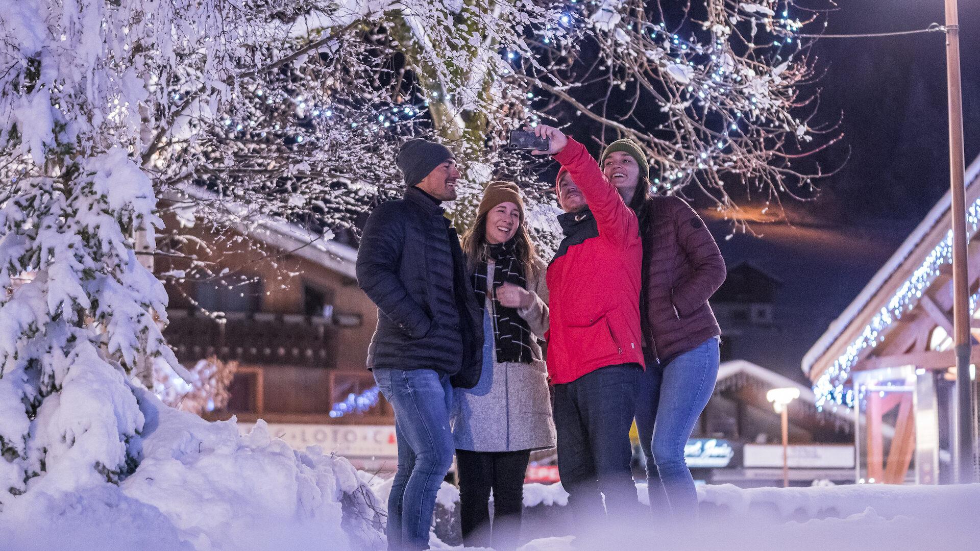 Amis se prenant en photo en hiver en soirée devant arbre enneigé et décoré