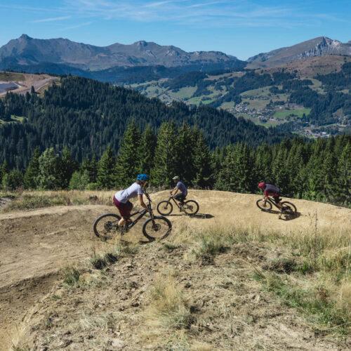 Trois personnes descendant une piste de VTT en montagne en été