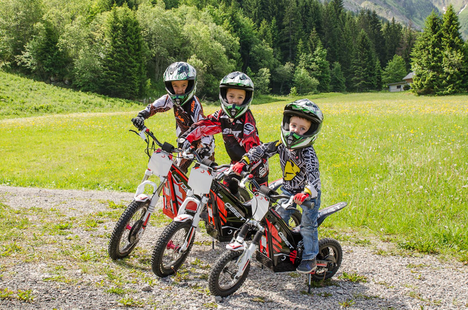 Trois enfants sur des motos électriques en été