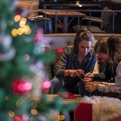 Amis assis dans un restaurant décoré pour noel et regardant leur téléphone
