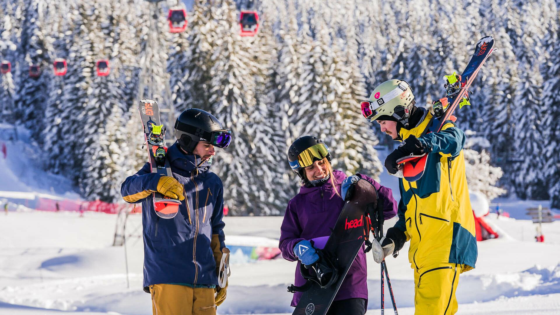 Skieurs et snowboardeuse discutant avec télécabine rouge derrière