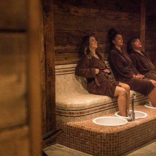 Trois personnes assis avec des peignoirs les pieds dans l'eau