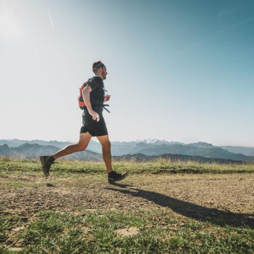 Homme faisant de la course à pied en été en montagne