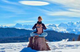Femme faisant du yoga en hiver assise sur un tronc d'arbre avec montagne derrière