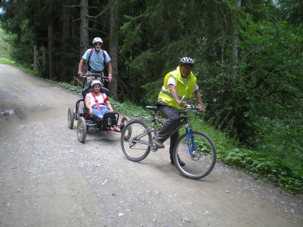 Three people riding MTBs, two of whom are Handi MTBs