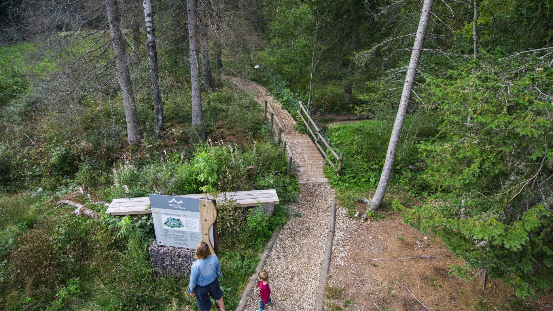 Femme et son enfant regardant un panneau explicatif Géopark Chablais. Chemin de promenade en forêt