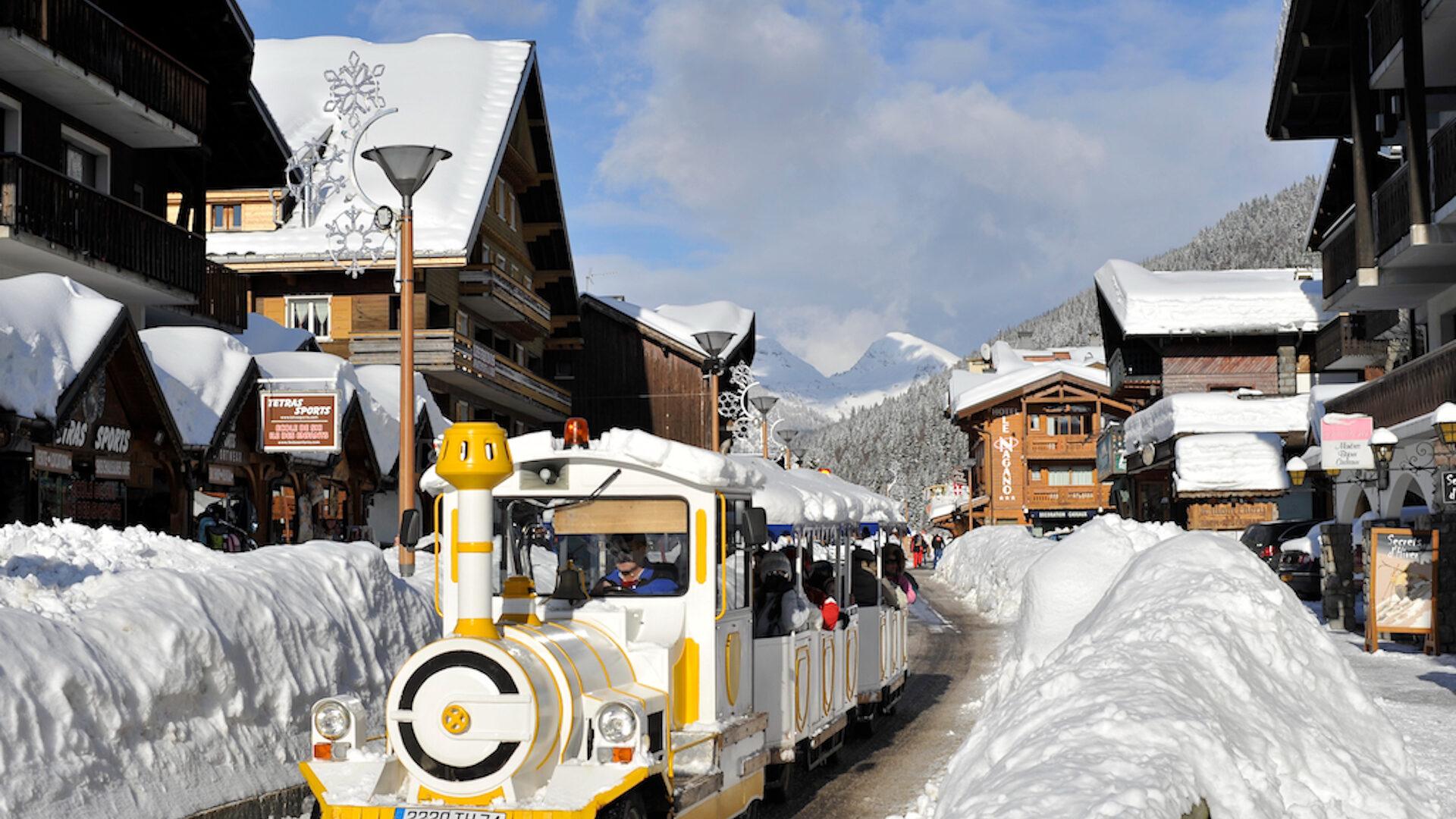 Petit train circulant dans un village de montagne en hiver