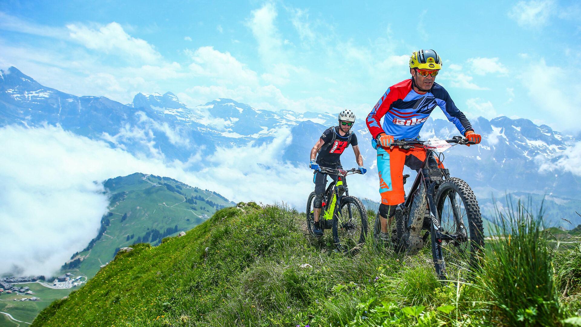 Hommes faisant du VTT en été sur les crêtes avec montagnes en fond