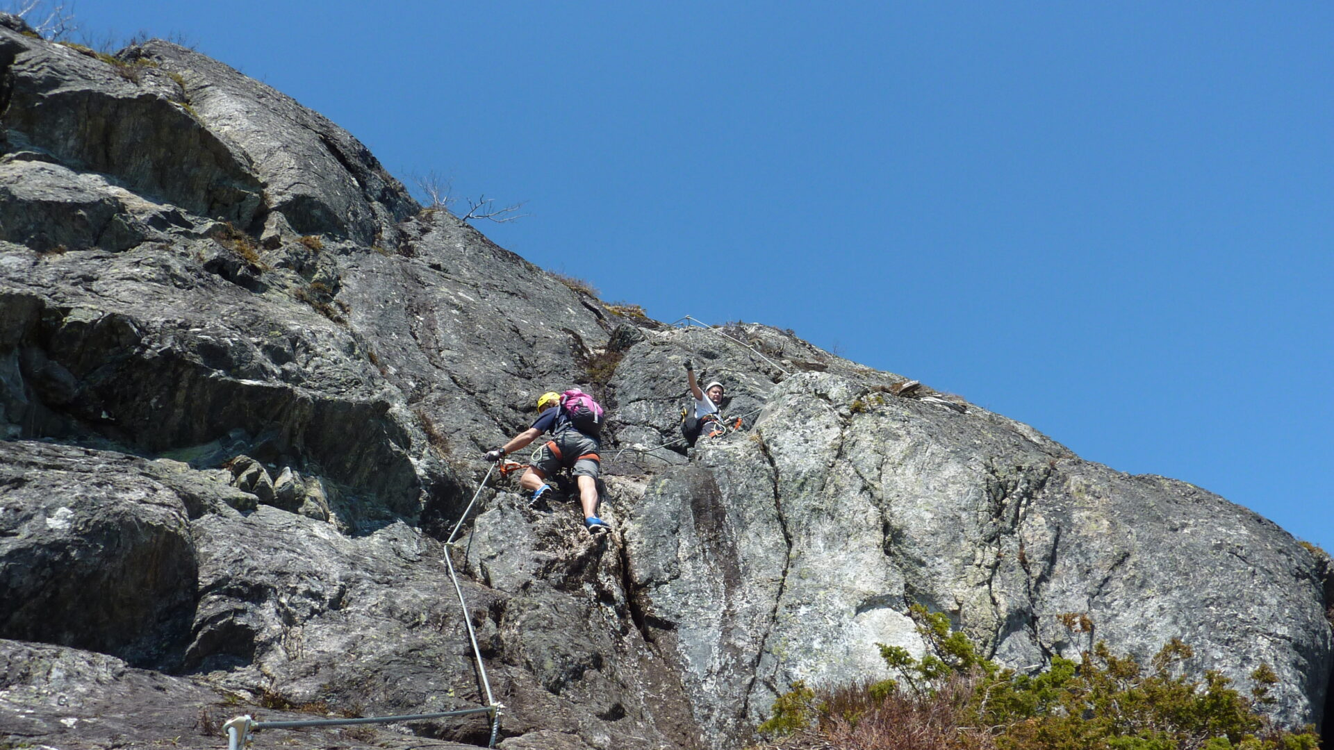 Personnes grimpant un rocher à l'aide d'une corde. Via ferrata