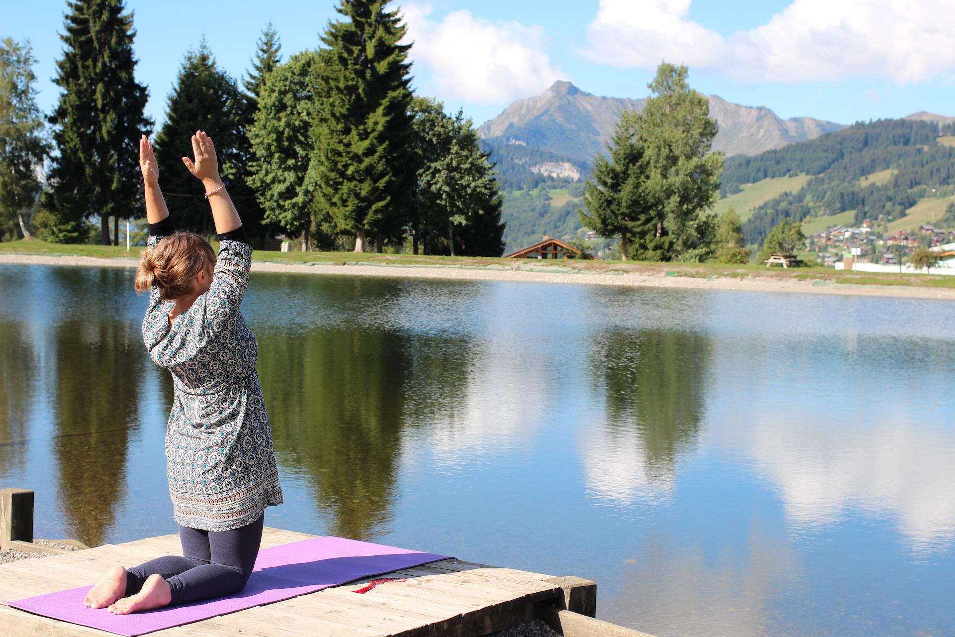 Femme faisant du yoga au bord d'un lac