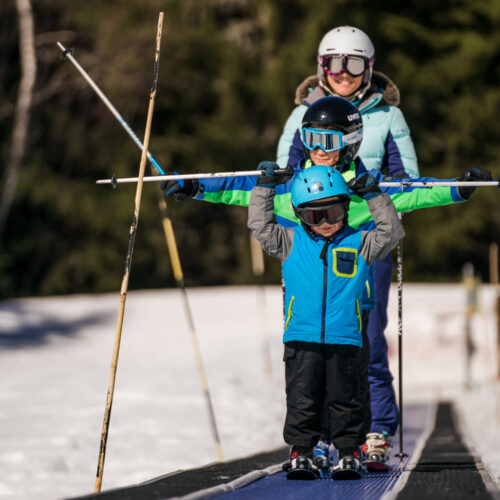Enfants et leur maman sur tapis en ski