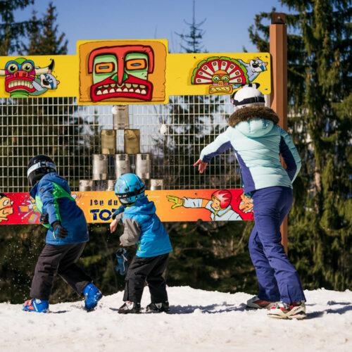 Famille jouant à un jeu sur le thème des indiens en hiver