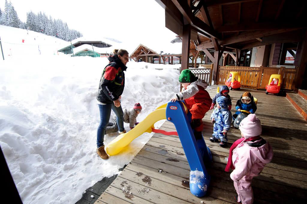 Enfants jouant dans la neige avec toboggan