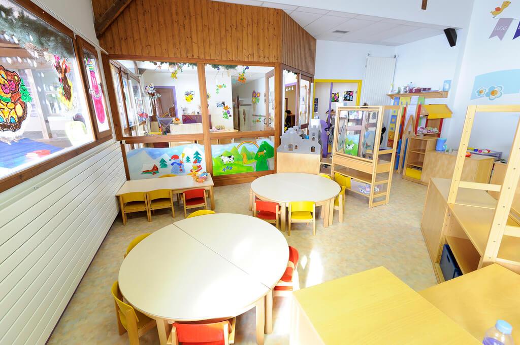 Salle principale d'une garderie avec tables, meubles et décorations