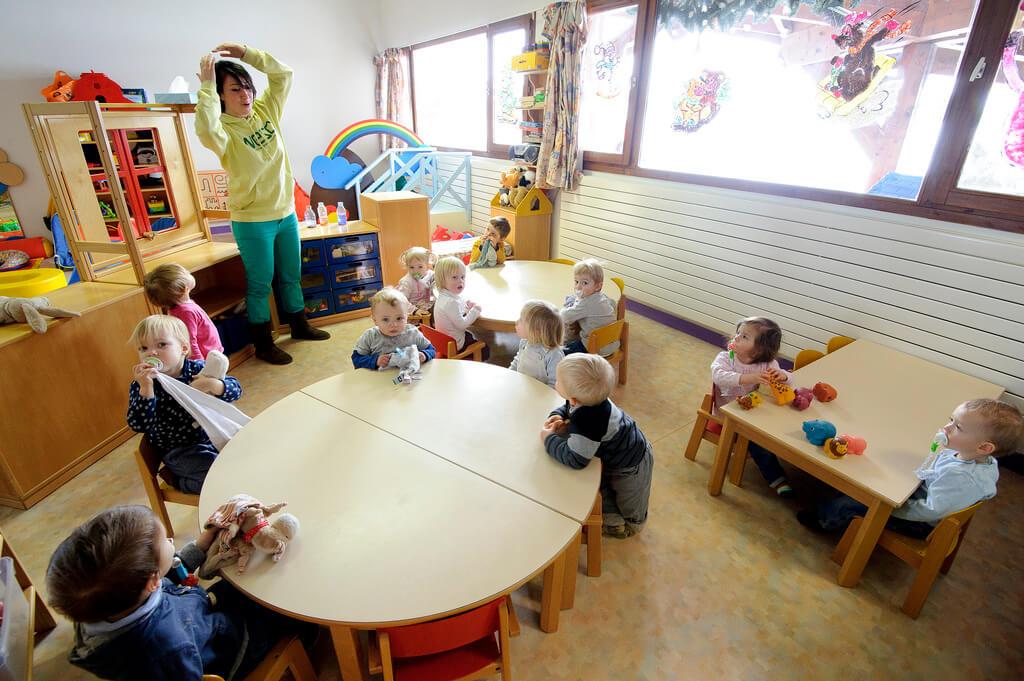 Enfants dans une garderie avec femme qui s'occupe d'eux