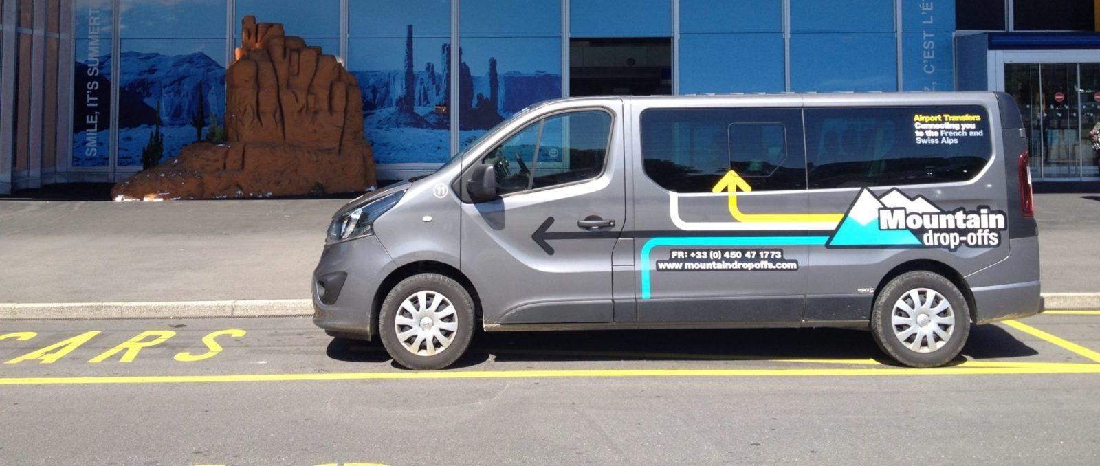 Grey transporter van parked near an airport