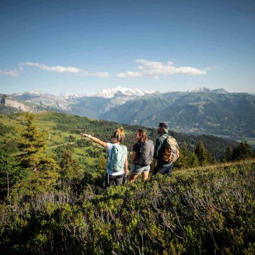 Groupe d'amis randonnant sur la crête de la Rosta et regardant le Mont Blanc